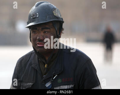 Datong, Shanxi, China. 12th Dec, 2018. Chinese coal miners leave the tunnels after finishing their shifts and walk back to housing in Datong, Shanxi Province (China's coal country), on December 12, 2018. China is the largest producer and consumer of coal in the world, making it the leading emitter of greenhouse gases from coal. China burns much more coal than reported, which has continued to complicate climate talks. Credit: Stephen Shaver/ZUMA Wire/Alamy Live News - Stock Photo
