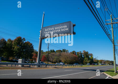 Electronic sign over highway that says, Active Shooter Take Cover Now. There is a blue sky and cars on the highway - Stock Photo
