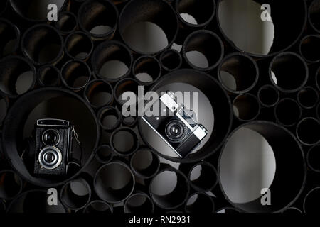Love for photography, creativity. Creativities.Two film cameras on black abstract background. Learning photography.