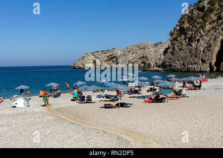 Karpathos island, Greece - September 5, 2018.  Swimmers, bathers lie on the sunbeds on the small beach of Amopi, popular beach near Pigadia. Dodecanes - Stock Photo