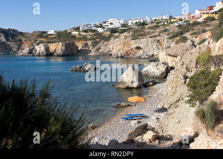 Karpathos island, small pebbles beach and umbrella in Amopi bay. Aegean sea, Dodecanese Islands, Greece - Stock Photo