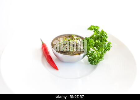 Raw homemade Argentinian green Chimichurri salsa or sauce isolated on a white background - Stock Photo