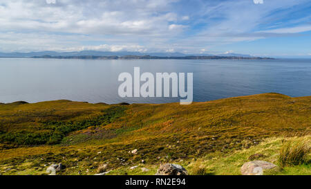Sun shines on the Hebridean islands of Rona and Skye, across a blue sea from the Applecross Peninsula in the Highlands of Scotland. - Stock Photo
