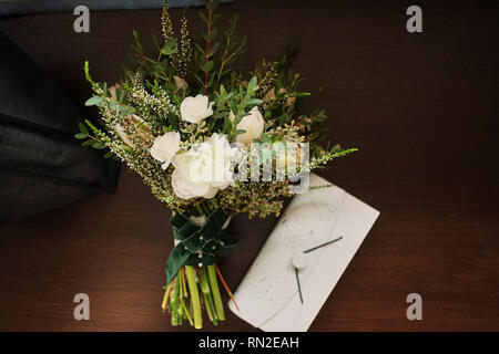 beautiful wedding bouquet lies on a wooden background,to a white clutch - Stock Photo