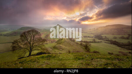 Landscape image of a vibrant sunrise through dramatic clouds over Parkhouse Hill in the UKs Peak District National Park. - Stock Photo