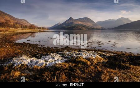 The distinctive shaped Pap of Glencoe mountain is reflected in the calm water of Loch Leven, a fjord-like inlet of the Atlantic Ocean, on a clear wint - Stock Photo