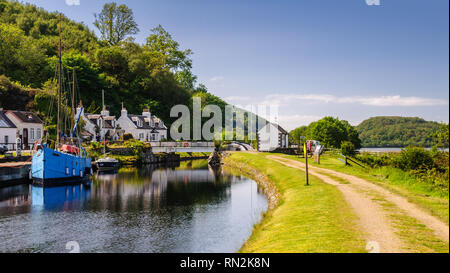 Crinan, Scotland, UK - June 3, 2011: A small yacht and fishing boat are moored beside traditional cottages on the Crinan Canal in the West Highlands o - Stock Photo