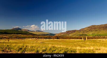 Ancient standing stones on moorland at Machrie Moor, with a mountain backdrop, on Scotland's Isle of Arran. - Stock Photo