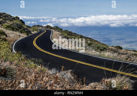 Maui Mountain Road:  The road from the top of Mt. Haleakalā begins above the clouds and descends to a tropical valley below. - Stock Photo