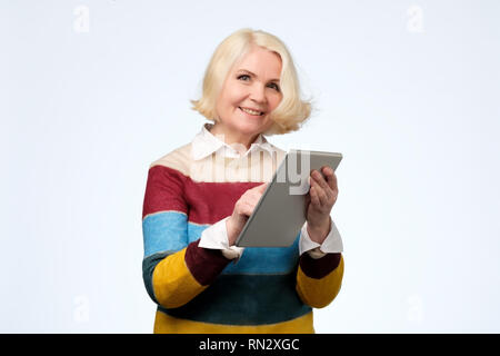 Senior woman using digital tablet surfing web media chatting online, smiling. - Stock Photo
