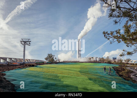 Man and women walking in the green ski slope on top of the new power plant in Copenhagen - Stock Photo