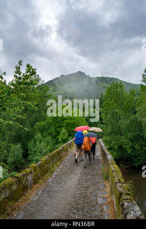 Conques, France - June 2015: a group of  pilgrims are crossing a small river on a stone made bridge along St James pilgrimage way in Conques - Stock Photo