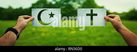 Religion conflicts as global issue concept. Two hands holding different faith symbols, Islam vs Christianity belief over green field nature. Relations - Stock Photo