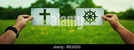 Religion conflicts as global issue concept. Two hands holding different faith symbols, Buddhism vs Christianity belief over green field nature. Relati - Stock Photo