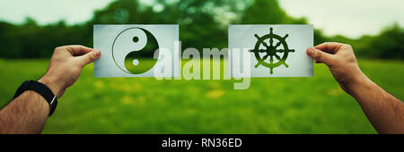 Religion conflicts as global issue concept. Two hands holding different faith symbols of China, Buddhism vs Taoism belief over green field nature. Rel - Stock Photo