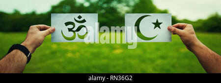 Religion conflicts as global issue concept. Two hands holding different faith symbols, Islam vs Hinduism belief over green field nature. Relationship  - Stock Photo