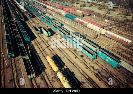 Aerial view of colorful freight trains on the railway station. Wagons with goods on railroad. Heavy industry. Industrial conceptual scene with trains. - Stock Photo