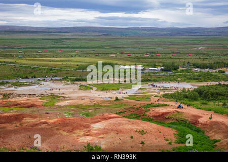 Tourists at Haukadalur geothermal valley waiting for the Great Geysir or Strokkur geysir to erupt. Geysir is one of the most popular tourist destinati - Stock Photo