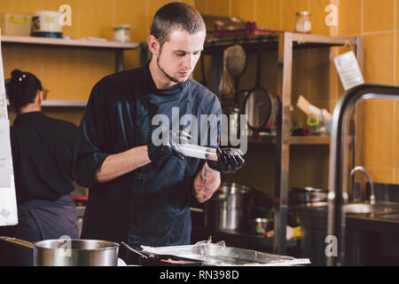 Theme cooking. A young Caucasian man in black uniform and latex gloves at a restaurant in the kitchen. Cooking mincers into a berry with a syringe. A  - Stock Photo