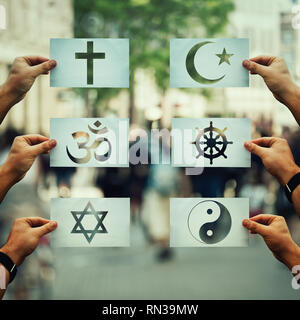 Religion conflicts as global issue concept. Human hands holding different paper with faith symbols over crowded street scene. Relations between differ - Stock Photo