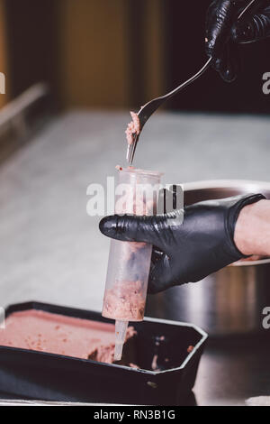 Theme cooking. Hands close up. young Caucasian man in black uniform and latex gloves in kitchen. restaurant prepares ground beef and leads into berry  - Stock Photo