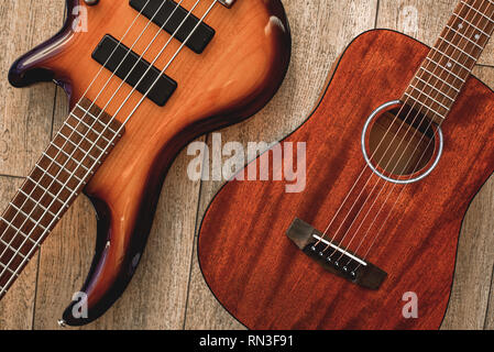 What to choose Top view on two cool musical instruments: acoustic and electric guitars are lying on the wooden floor in a music shop. Musical instruments. Music concept. - Stock Photo