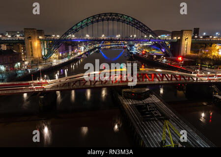 Newcastle, England, UK - February 3, 2019: The iconic Tyne Bridge and Swing Bridge between Newcastle and Gateshead are lit at night and reflected in t - Stock Photo