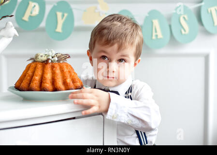 Little smiling boy is waiting for his piece of Easter cake - Stock Photo