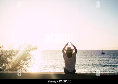 cute girl with cowbly summer style hat viewed from back doing hearth sign with hands - sun backlight and ocean with boat in background - freedom and e - Stock Photo