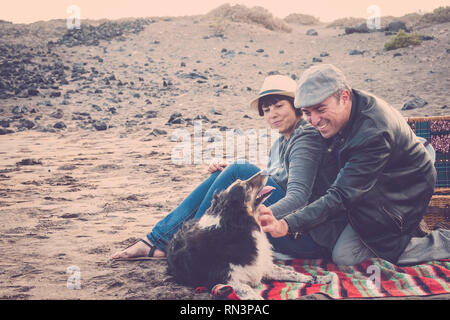 Alternative vintage style colors couple having fun in outdoor leisure activity picnic with adorable puppy dog - pet therapy concept for cheerful middl - Stock Photo
