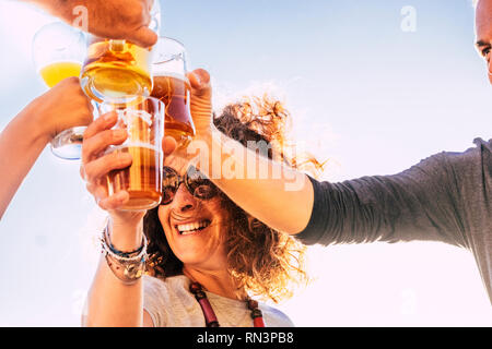Close up of people toasting and clinking together with happy and joy and having fun - cheerful people with beer and drinks laughing in friendship - mi - Stock Photo