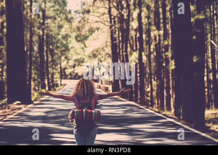 Eternity and success satisfaction life concept with lonely girl curly hai rin the middle of long road in the forest with open arms and backpack - wand