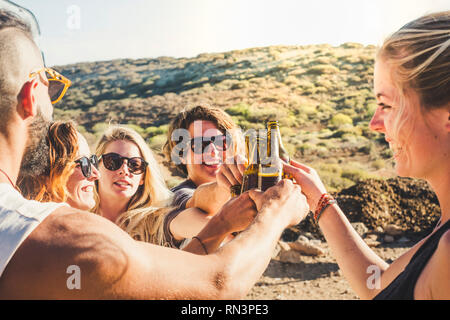 Group of young caucasian people boys and girls clinking together beer bottles in natural celebration day - enjoying outdoor and friendship lifestyle - - Stock Photo