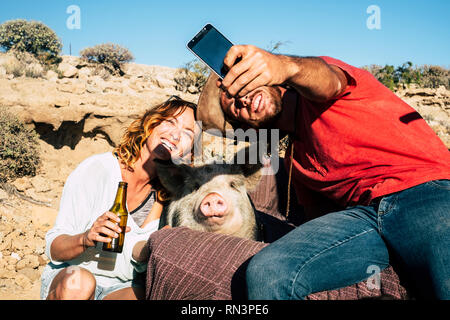 Alternative family or friends with young man and woman smiling while take a selfie with a domestic pig in the middle - everybody smile for the camera  - Stock Photo