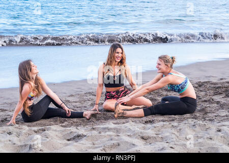 Three young beautiful girls doing stretching exercises at the beach in outdoor sport activity - have fun and enjoy the healthy lifestyle in friendship - Stock Photo