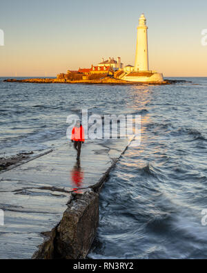 A man stands on the St Mary's Island Causeway while the setting sun illuminates St Mary's Lighthouse on the coast of Whitley Bay in Tyneside. - Stock Photo