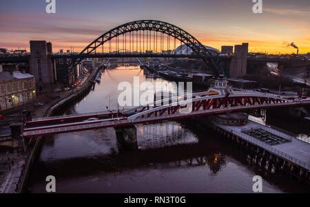 Newcastle, England, UK - February 5, 2019: The sun rises behind the iconic Tyne Bridge and swing bridge between Newcastle and Gateshead on the River T - Stock Photo