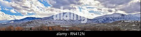 Winter Panorama of Oquirrh Mountain range snow capped, which includes The Bingham Canyon Mine or Kennecott Copper Mine, rumored the largest open pit c - Stock Photo