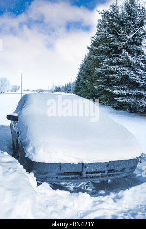 Car stuck and covered in thick snow after Winter snow storm blizzard covered entered landscape. - Stock Photo