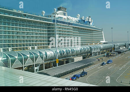 New Shanghai Baoshan Cruise Terminal with Royal Caribbean's mega cruise ship Quantum of the Seas towering over it. - Stock Photo