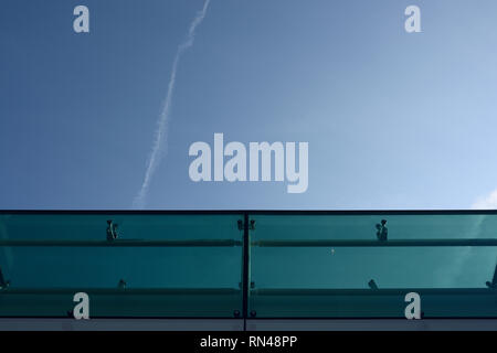Green tinted glass panels, curtain wall detail, structural glass and stainless steel fittings, with aircraft contrail against blue sky - Stock Photo