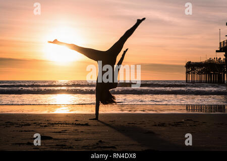 woman doing a cartwheel on the beach at sunset - Stock Photo