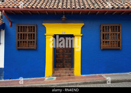 Stylish colonial exterior with wooden carved door and blue-yellow wall (complementary colour contrast) in La Candelaria. Bogota, Colombia. Sep 2018 - Stock Photo