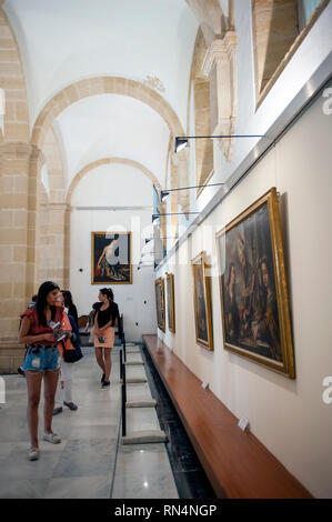 Tourists look at paintings from Seville's 17th century Golden Age in the Sala del Pabellon of Seville Cathedral. Built on the site of the Moorish 12th - Stock Photo