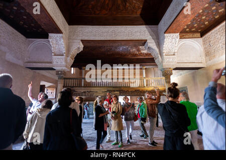 Tourists inside the 14th century Mexuar at the Alhambra, a 13th century Moorish palace complex in Granada, Spain. Built on Roman ruins, the Alhambra w - Stock Photo