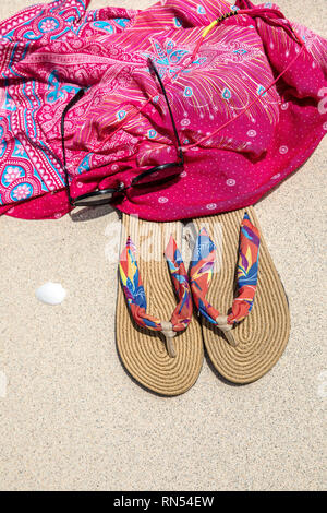 background sand background summer slippers and Coral Color Pareo sunglass in Gili Trawangan, Indonesia - Stock Photo