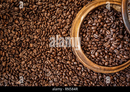 Fresh roasted arabica and robusta coffee beans. Coffee in a wooden bowl - Stock Photo