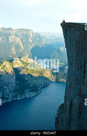 A lone man sits on top of the Pulpit Rock / Preikestolen or Prekestolen overlooking Lysefjord in Norway - Stock Photo