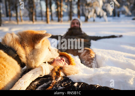 Girl Playing with Dog in Snow - Stock Photo