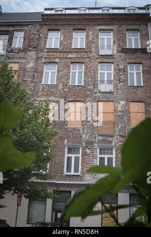 boarded up residence in tenement housing block as viewed from outside - Stock Photo